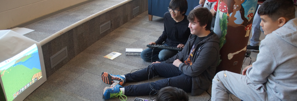 Male students sitting on carpet playing a coding game