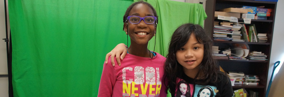 Two female students standing in front of a green screen